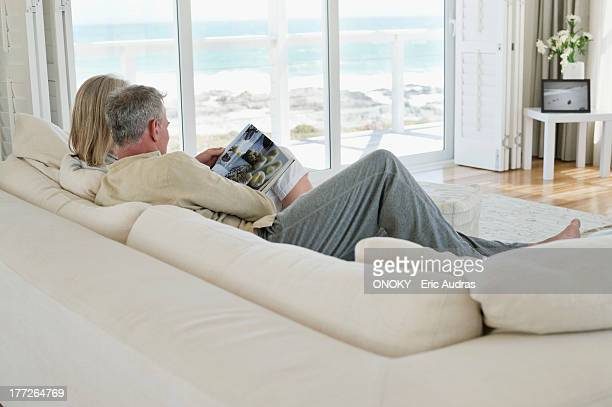 Couple sitting on a couch and reading a magazine