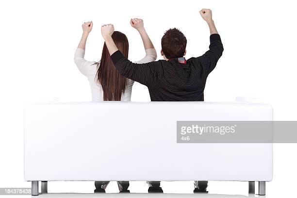 Paar sitzen auf couch mit seine Arme hoch