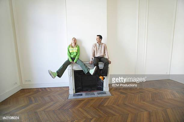 Couple Sitting on a Fireplace in an Empty New House
