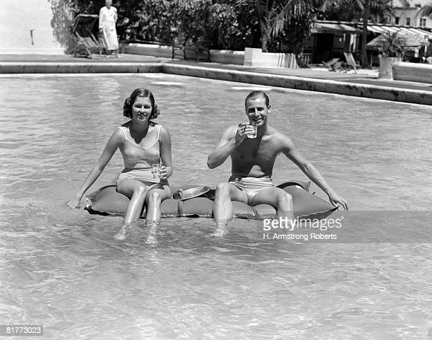Couple Sitting On A Float In A Swimming Pool Wearing Bathing Suits Holding Drinks In Thier Hands Smiling Spectator Serving Tray Sparkle.