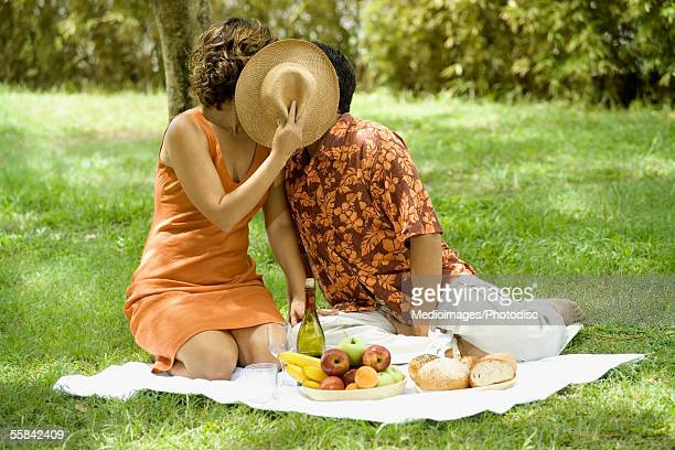 Couple sitting on a lawn holding a hat in front of their face while kissing