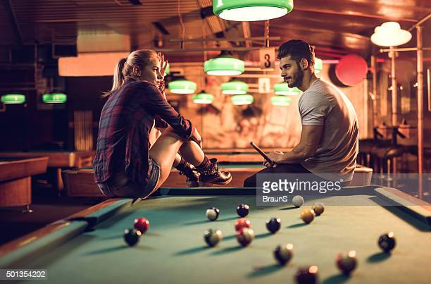 Couple sitting on a pool table in pub and talking.