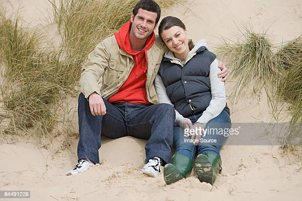Couple sitting on a sand dune