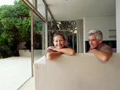 Couple Sitting on a Sofa in Their Home With Open Patio Doors Leading onto a Garden