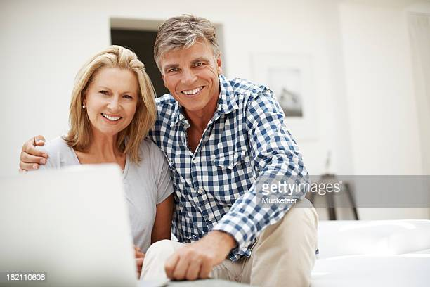 Couple sitting on a sofa looking into camera