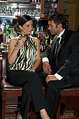 Couple sitting on barstools, talking and drinking, three quarter length