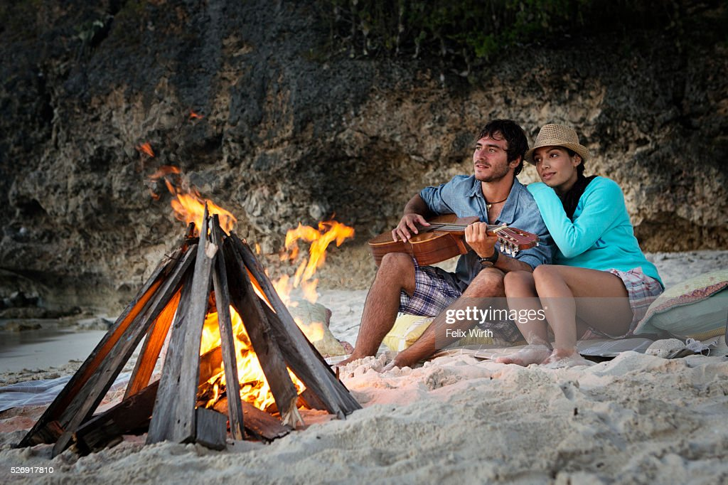 Couple sitting on beach at campfire : Stock Photo
