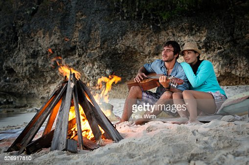 Couple sitting on beach at campfire : Foto de stock