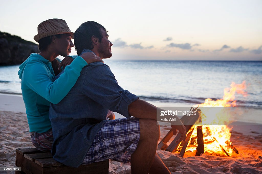 Couple sitting on beach at campfire : ストックフォト