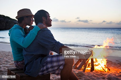 Couple sitting on beach at campfire : Stock-Foto