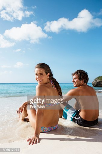 Couple sitting on beach : Bildbanksbilder