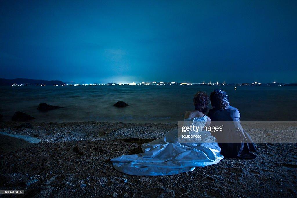 Couple sitting on beach under moon : Stock Photo