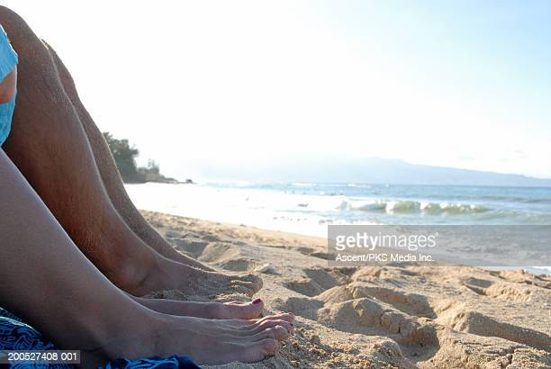 Couple sitting on beach with toes in the sand, low section