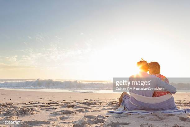 Couple sitting on beach wrapped in a towel