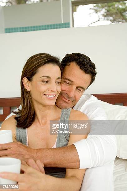 Couple sitting on bed, indoors