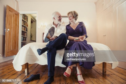 Couple sitting on bed, man putting on shoes