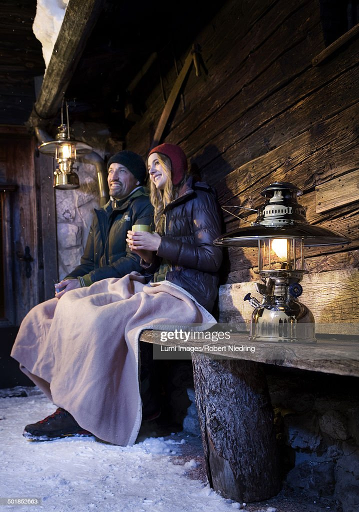 Couple Sitting On Bench In Front Of Log Cabin, Tyrol, Austria, Europe
