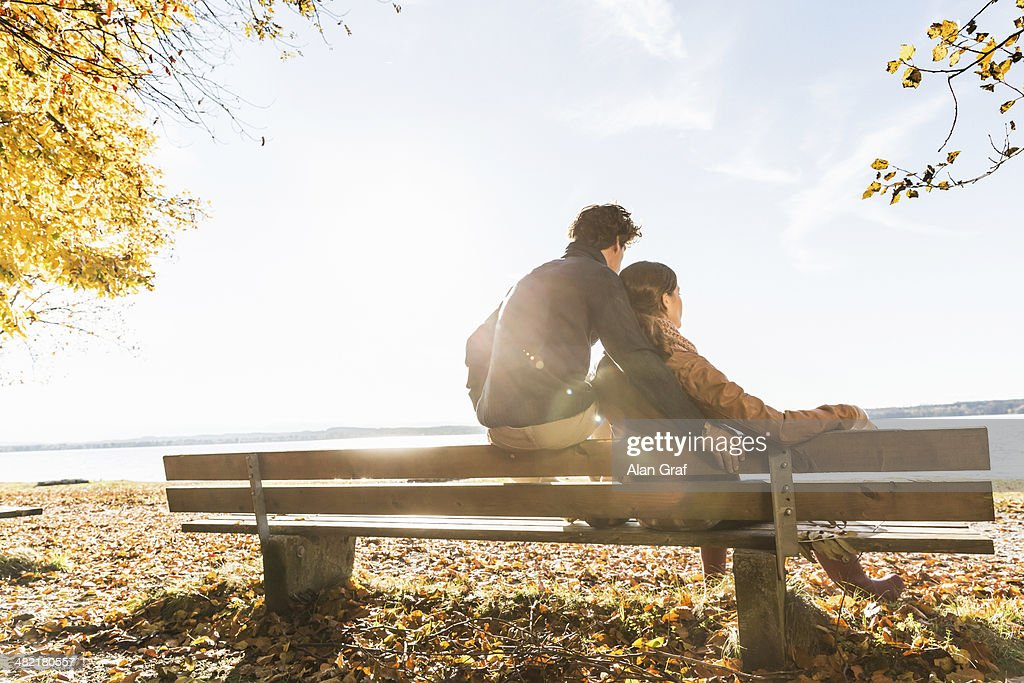Couple sitting on bench, rear view