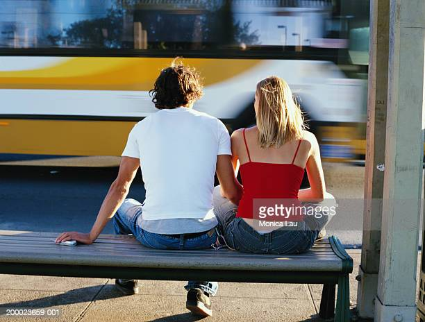 Couple sitting on bench while bus passes, rear view (blurred motion)