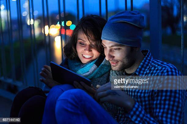 Couple sitting on bridge and using digital tablet at night