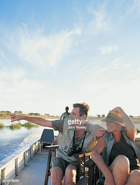 Couple Sitting on Chairs on a River Boat in Africa Looking at the View