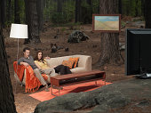 A couple sitting on coach watching television outdoors in the woods