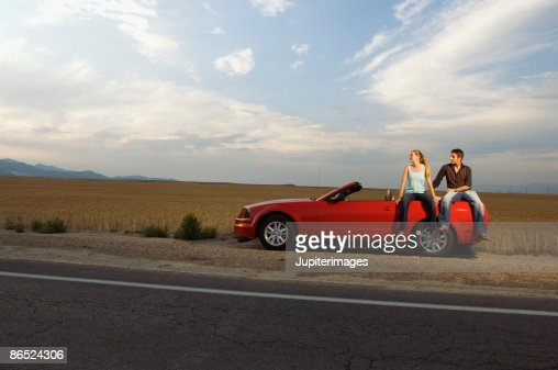 Couple sitting on convertible on desert road stock foto for 125 12th street 4th floor oakland ca 94607