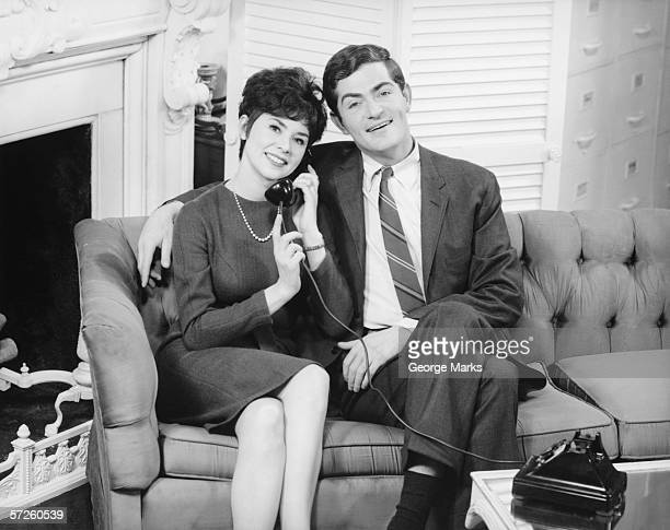 Couple sitting on couch in living room, woman on phone, (B&W), portrait