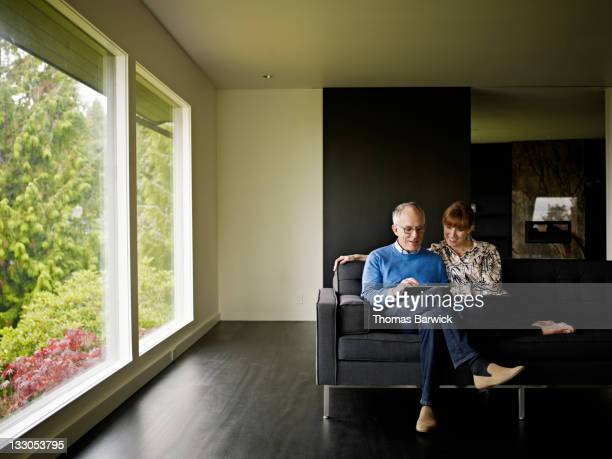 Couple sitting on couch looking at digital tablet
