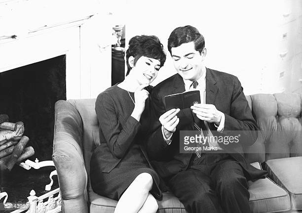 Couple sitting on couch, man holding small book, (B&W)