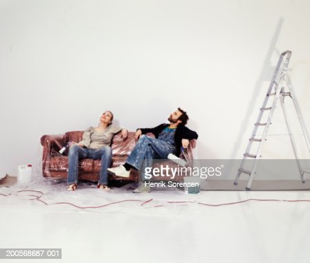Couple sitting on couch taking break while painting flat