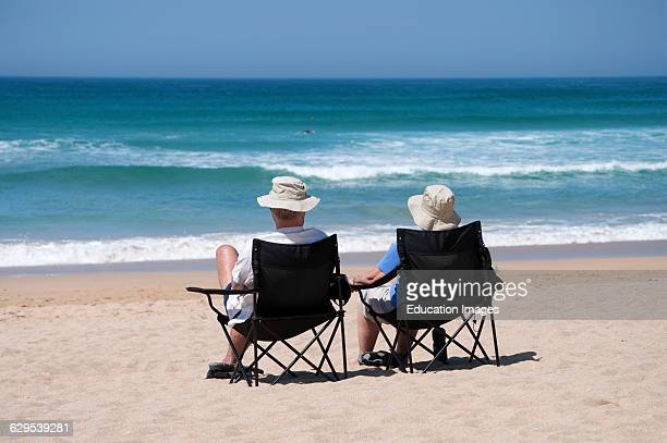 A couple sitting on deck chairs by the sea in Cornwall England UK