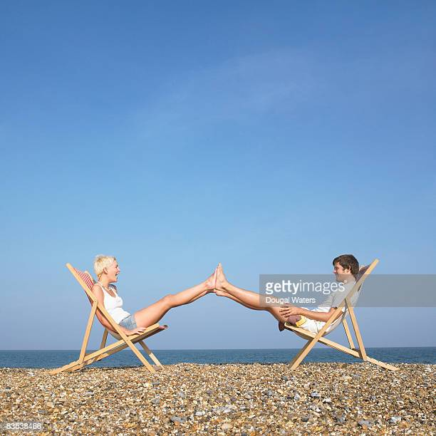 Couple sitting on deck chairs with feet together.