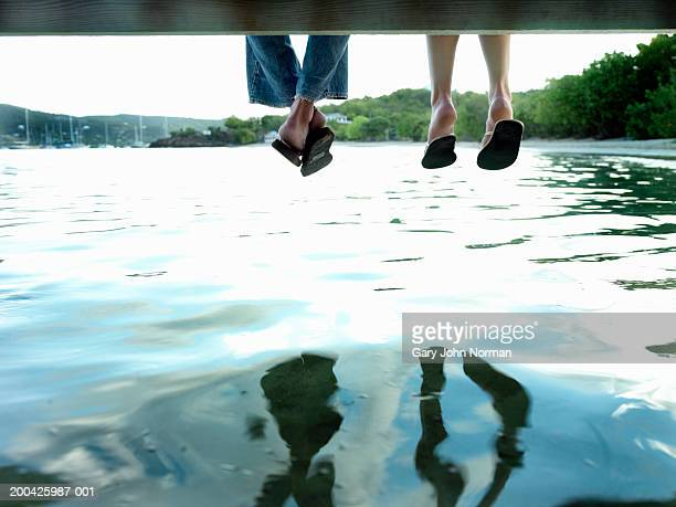 Couple sitting on dock, low section, rear view