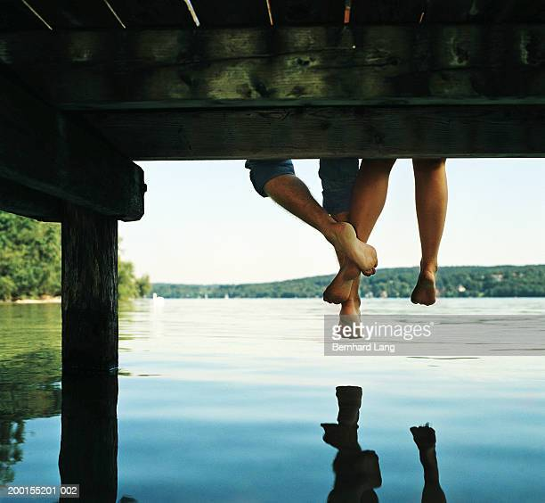 Couple sitting on edge of jetty, legs touching, low section