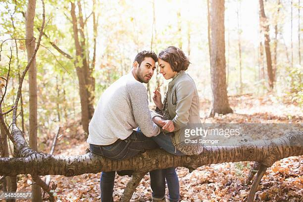 Couple sitting on fallen tree in autumn forest