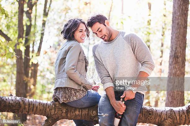 Couple sitting on fallen tree opening bottle of rose wine in forest