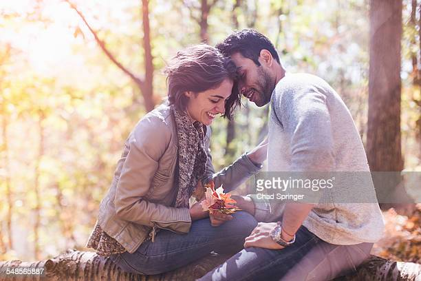 Couple sitting on fallen tree with autumn leafs in forest
