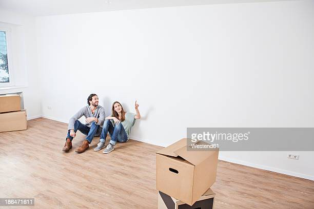 Couple sitting on floor and pointing at wall