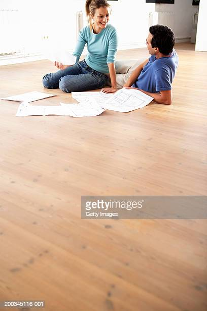 Couple sitting on floor, by blue prints, smiling
