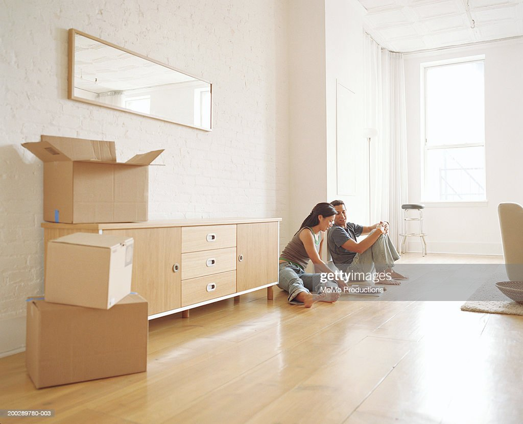 Couple sitting on floor in new apartment, looking at magazine