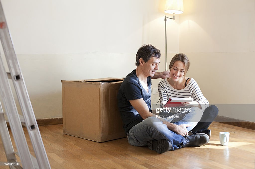 couple sitting on floor in their new, empty house : Stock Photo