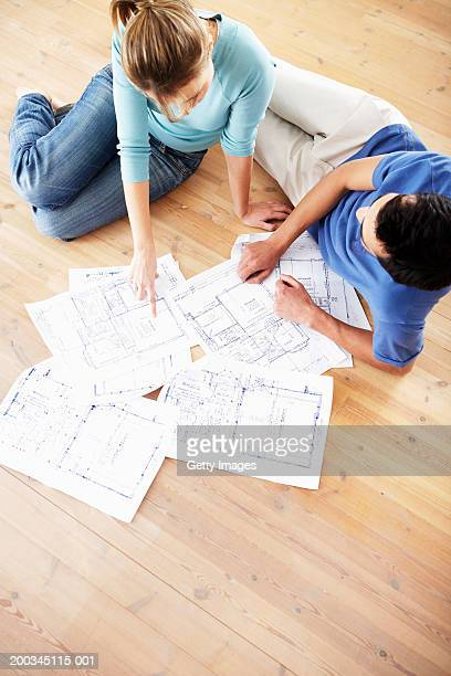 Couple sitting on floor, looking at blue prints, elevated view