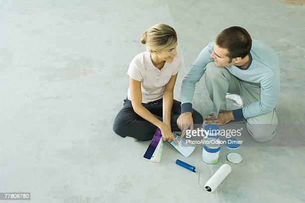 Couple sitting on floor looking at color swatches