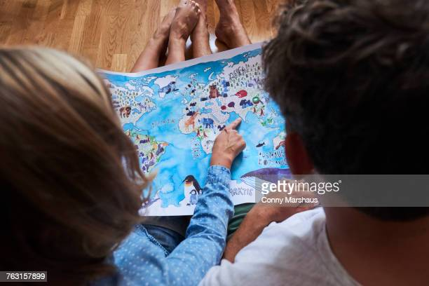 Couple, sitting on floor, looking at picture map, rear view