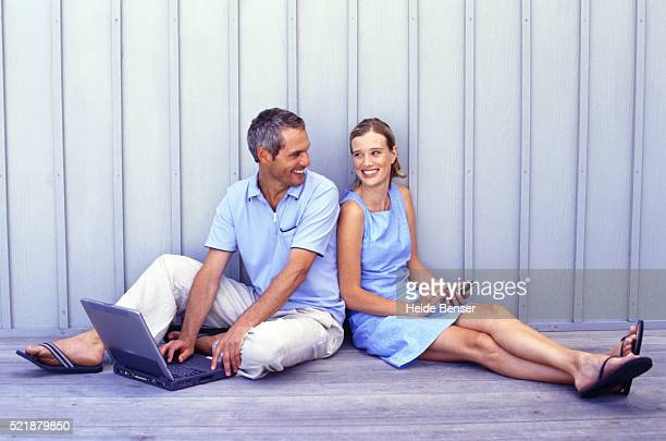 Couple sitting on floor using handheld and laptop