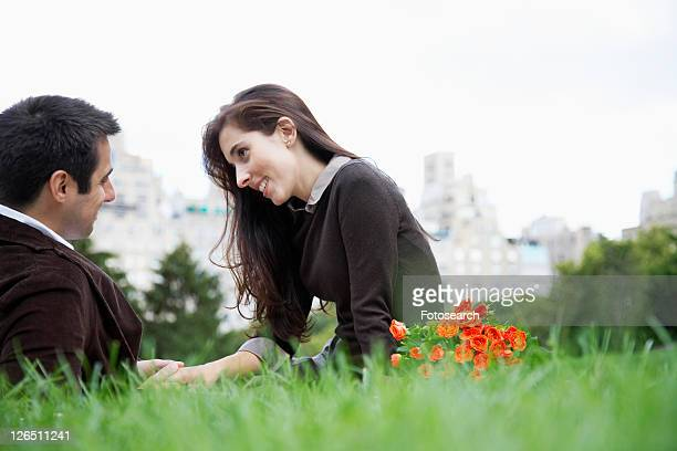 Couple sitting on grass and holding hands (low angle view)