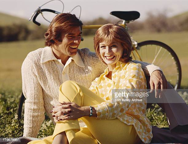 Couple sitting on grass, bicycle in background