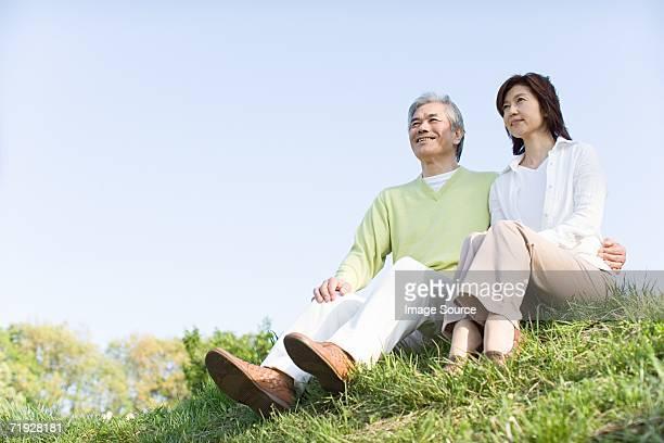 草の上に座ってカップル