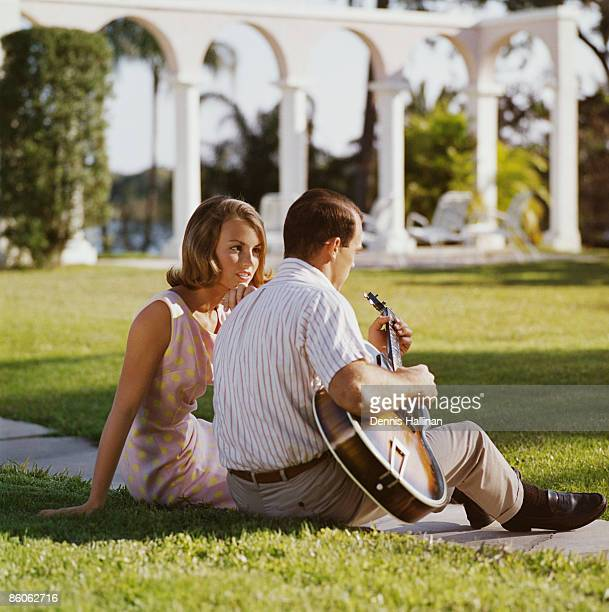Couple sitting on grass playing guitar